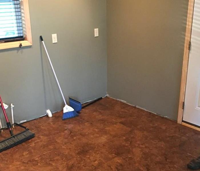 Brown wood flooring with a broom standing on it.