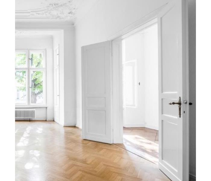 Two white doors open in a white room.