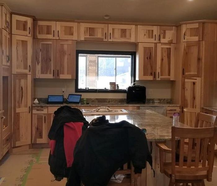 Kitchen with raw wood cabinets.