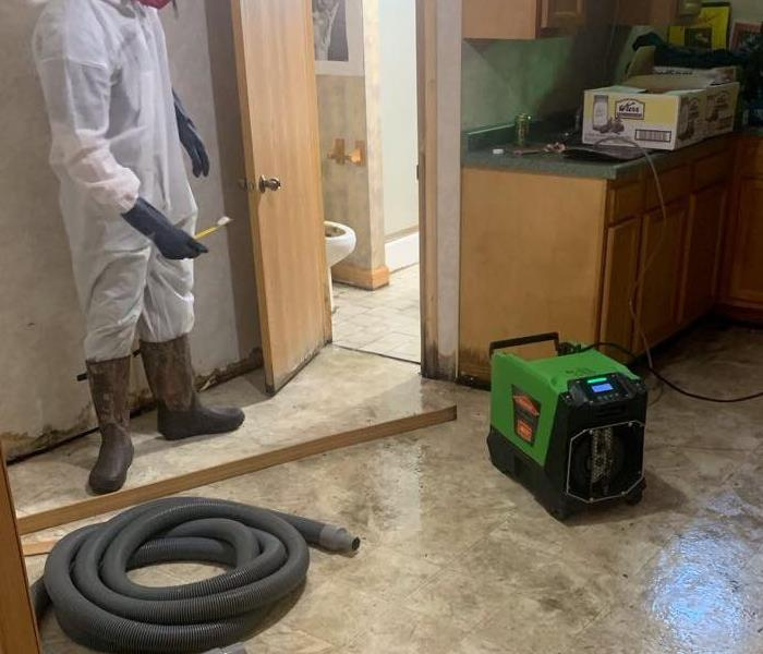 Kitchen area with a SERVPRO employee and air movers.