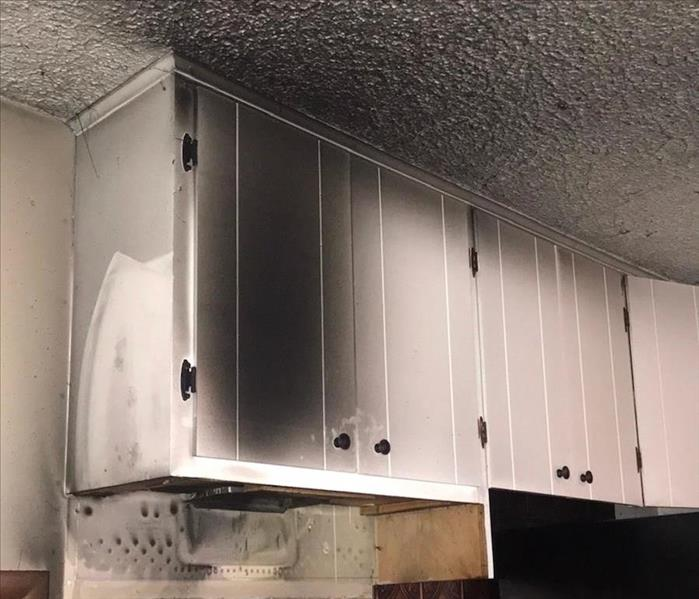 White kitchen cabinets stained with dark black soot.