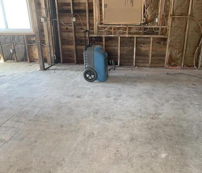 Room with concrete flooring and a blue air mover.