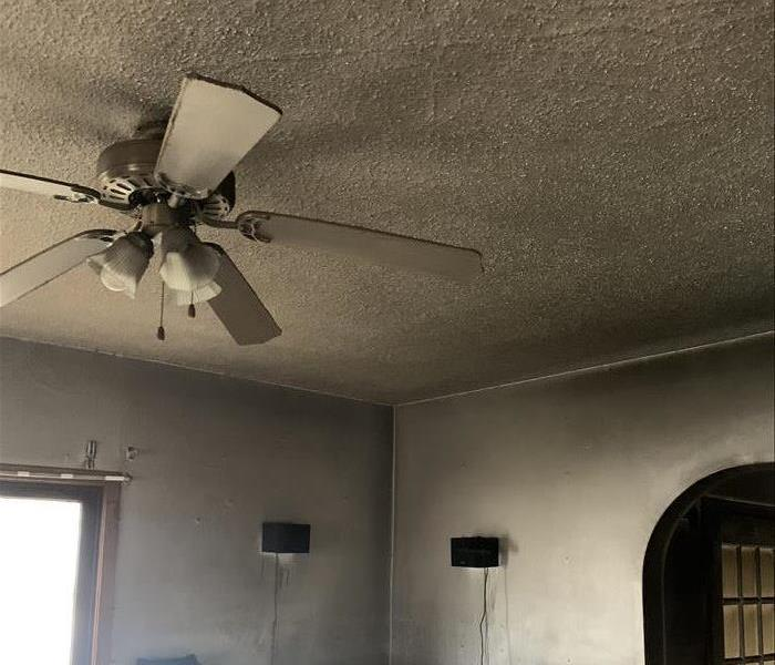 Living room and ceiling covered in dark grey soot.