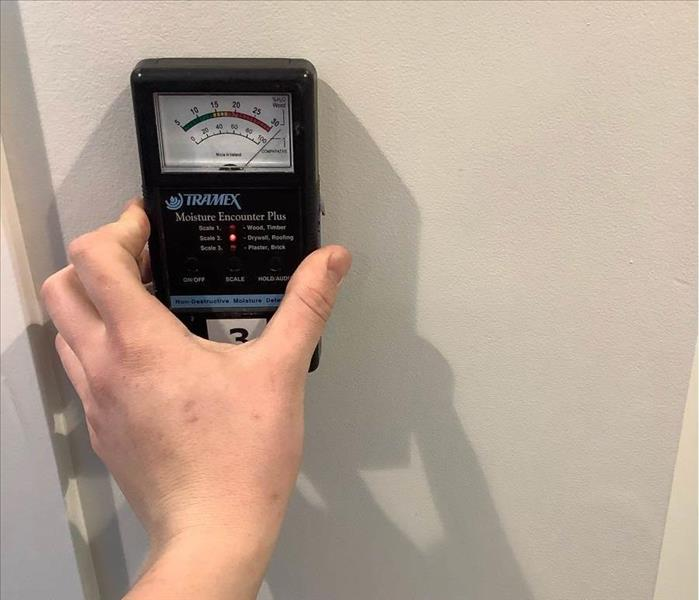 Moisture meter up against a wall.